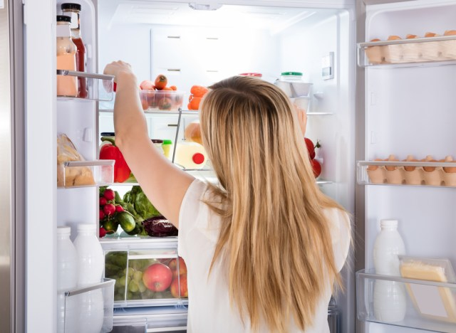 Hungry woman looking for food in fridge