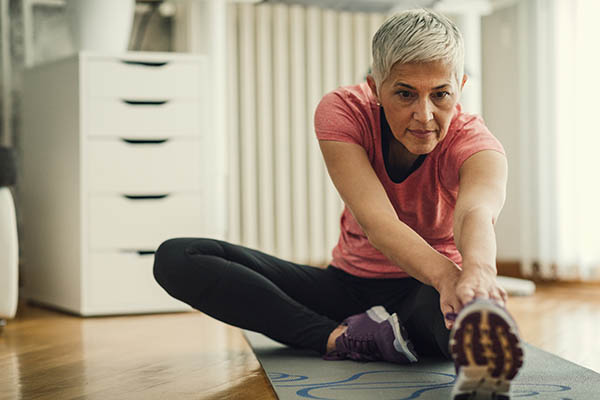 Woman stretching on the floor at home