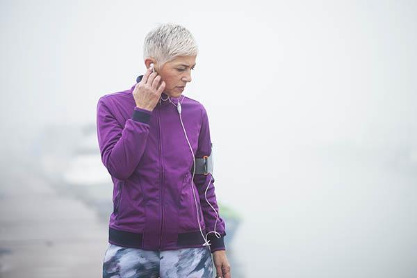 mature woman jogging through fog