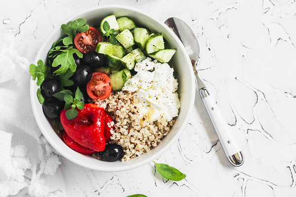 Bowl of quinoa salad with cucumbers, tomatoes, and red pepper