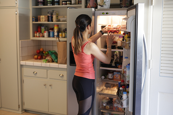 Woman putting away groceries and meal prepping