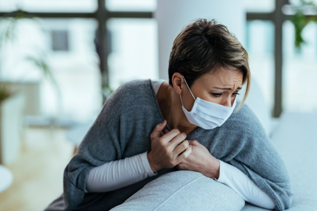 Young woman feeling sick and having chest pain while coughing at home.