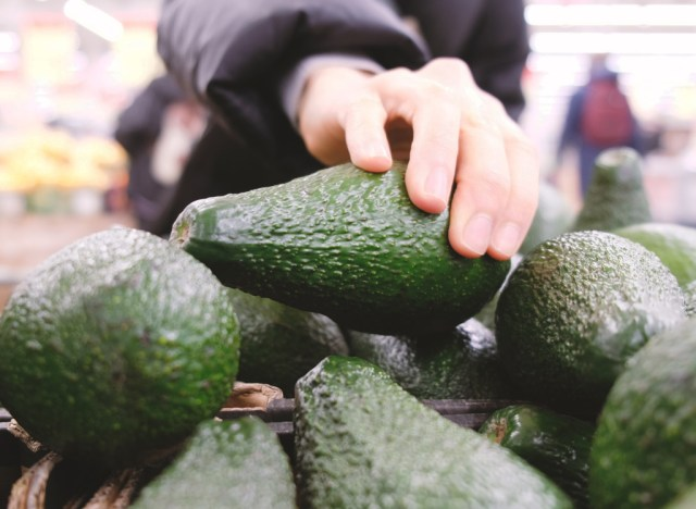 Pick avocado at grocery store