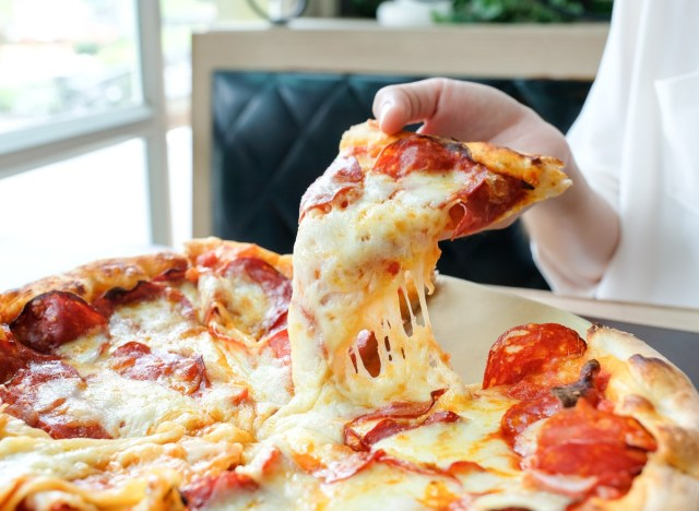 Woman grabbing slice of cheese pizza with pepperoni meat lovers