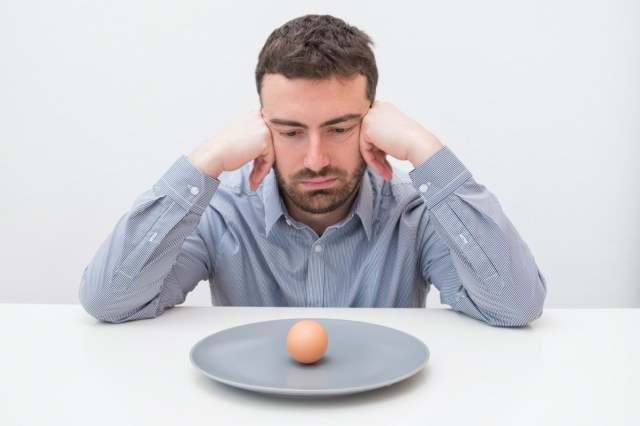 Hungry man feeling sad in front of a dish with an egg
