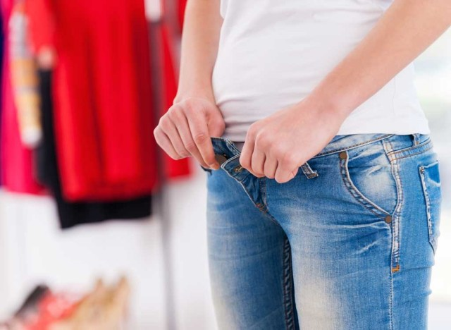 Bloated woman putting on jeans