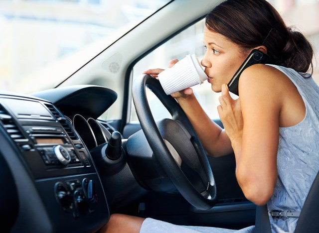 Busy woman driving car and drinking coffee