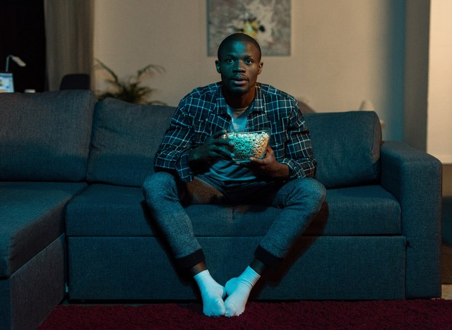 man watching tv on couch holding popcorn bowl