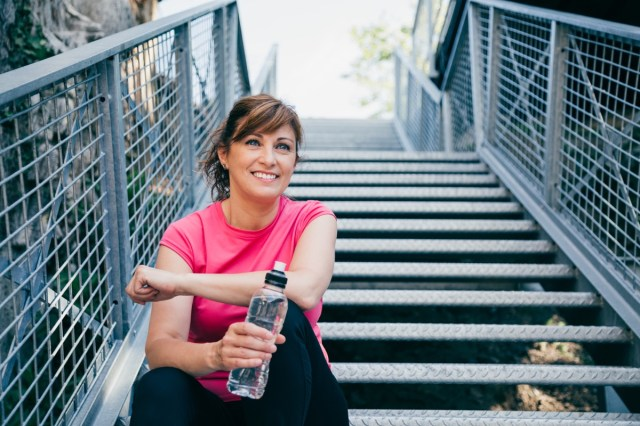 middle aged woman sitting on metallic stairs relaxing before running outdoors holding a water bottle
