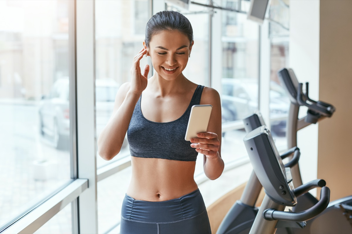 woman in sportswear choosing music for fitness on her smartphone while standing against treadmills at gym