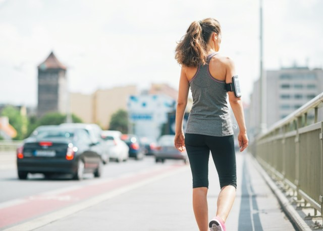 woman walking for exercise in a city