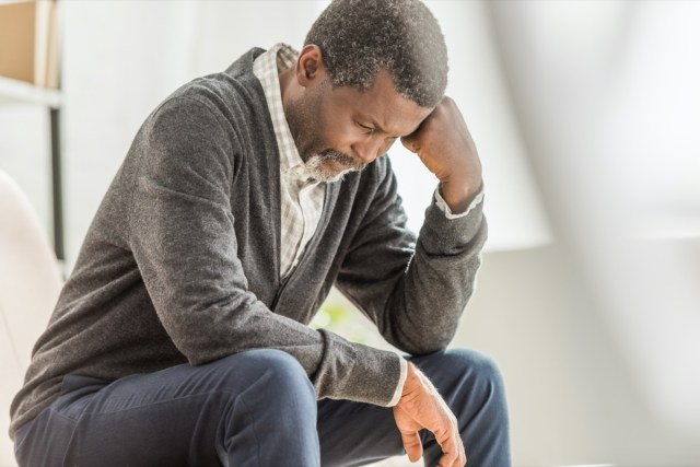 selective focus of depressed african american man sitting with bowed head