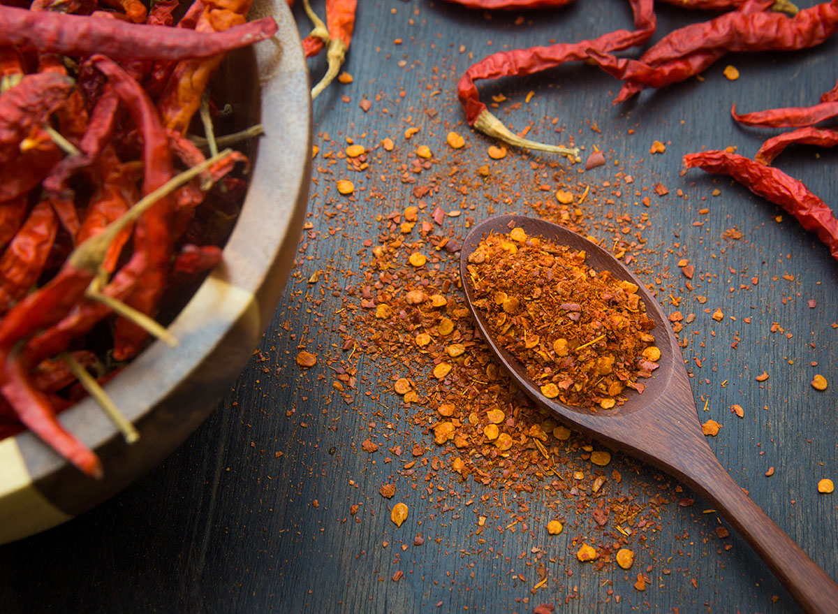 cayenne pepper on wooden spoon and table
