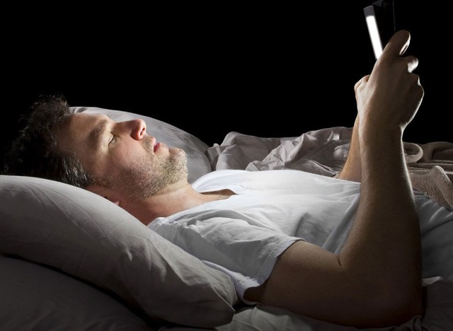 Man laying in bed on phone - best ways to speed up your metabolism