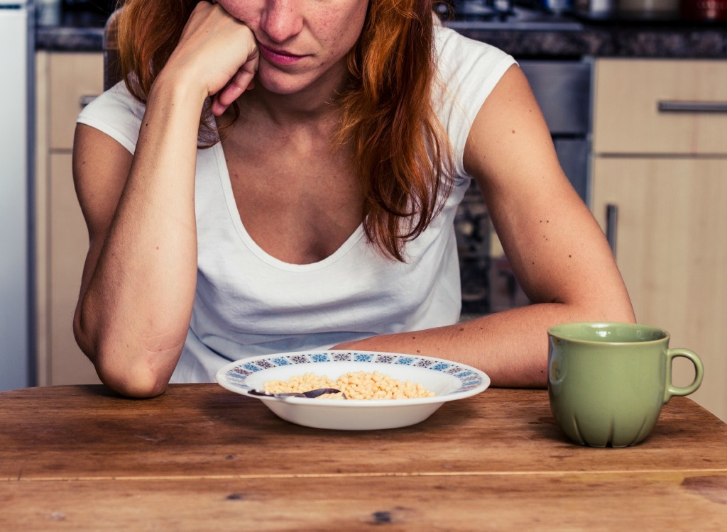 Woman looking bored staring at bowl of cereal