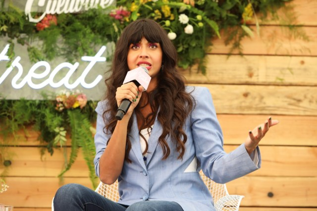 jameela jamil holding a microphone in a blue blazer