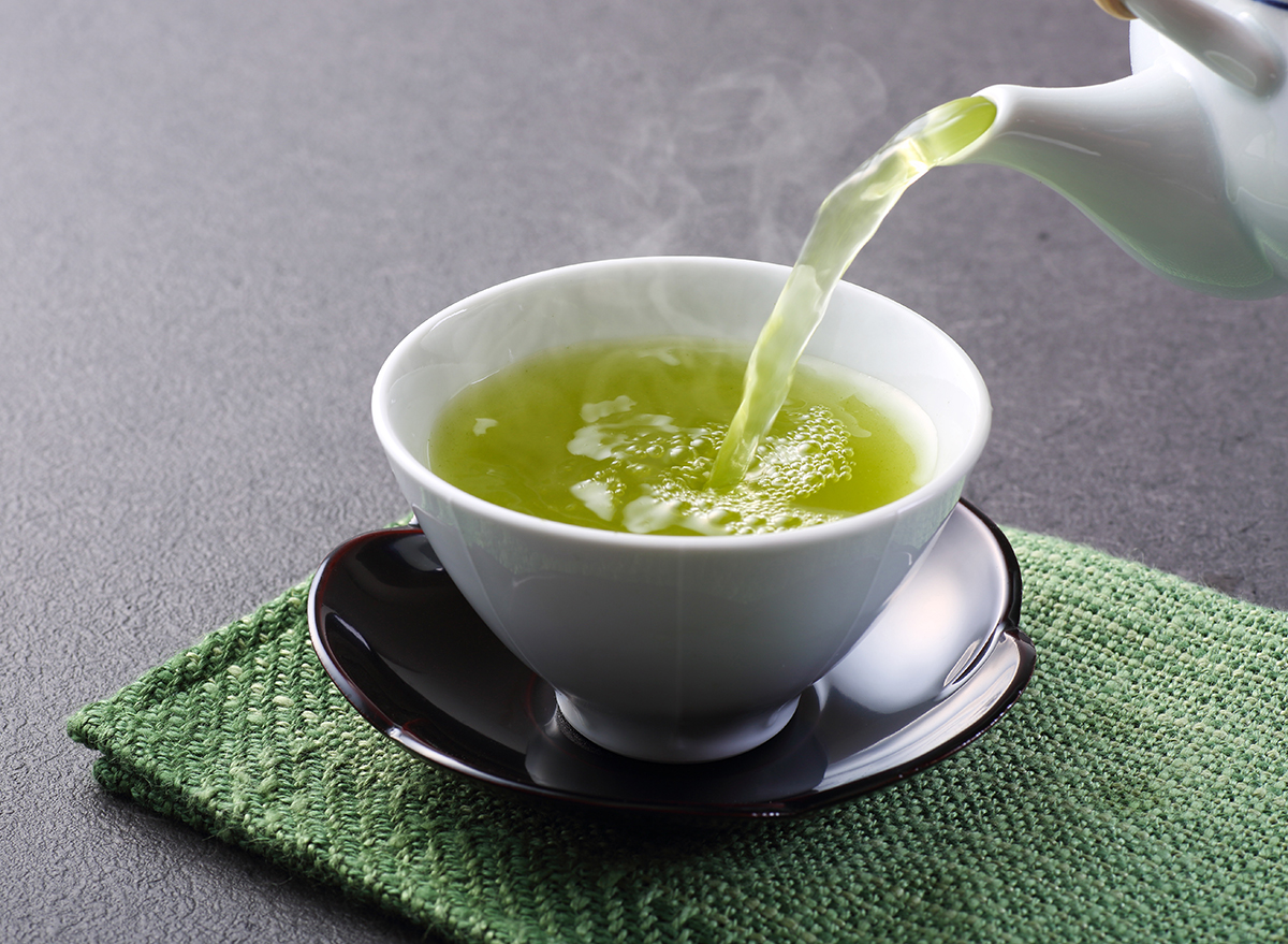 green tea being poured into cup