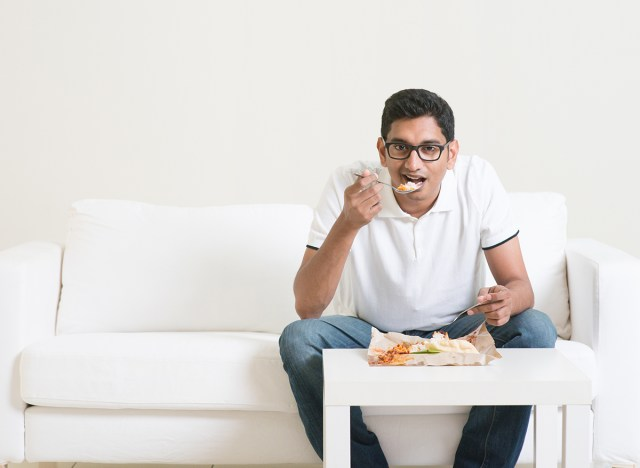 man eating dinner sitting on white couch