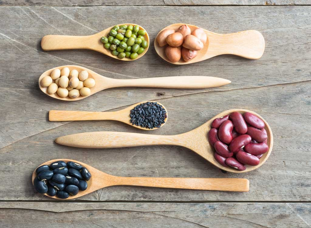 different beans on wooden spoons