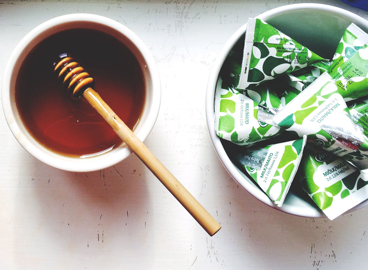 Honey in bowl next to bowl of sugar packets