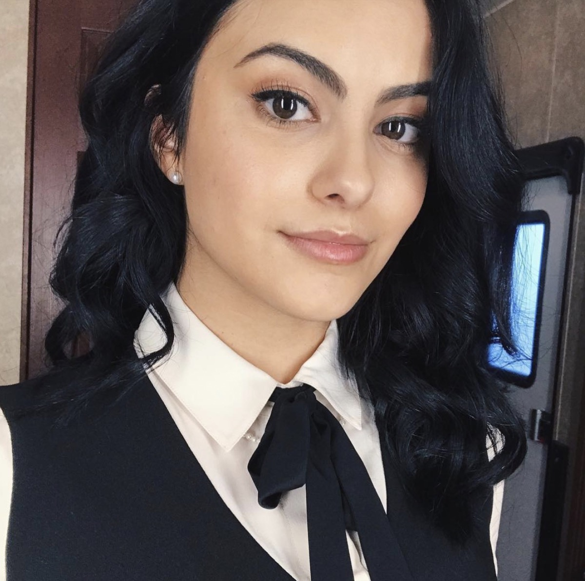 camila mendes wearing white collared shirt and black bow tie