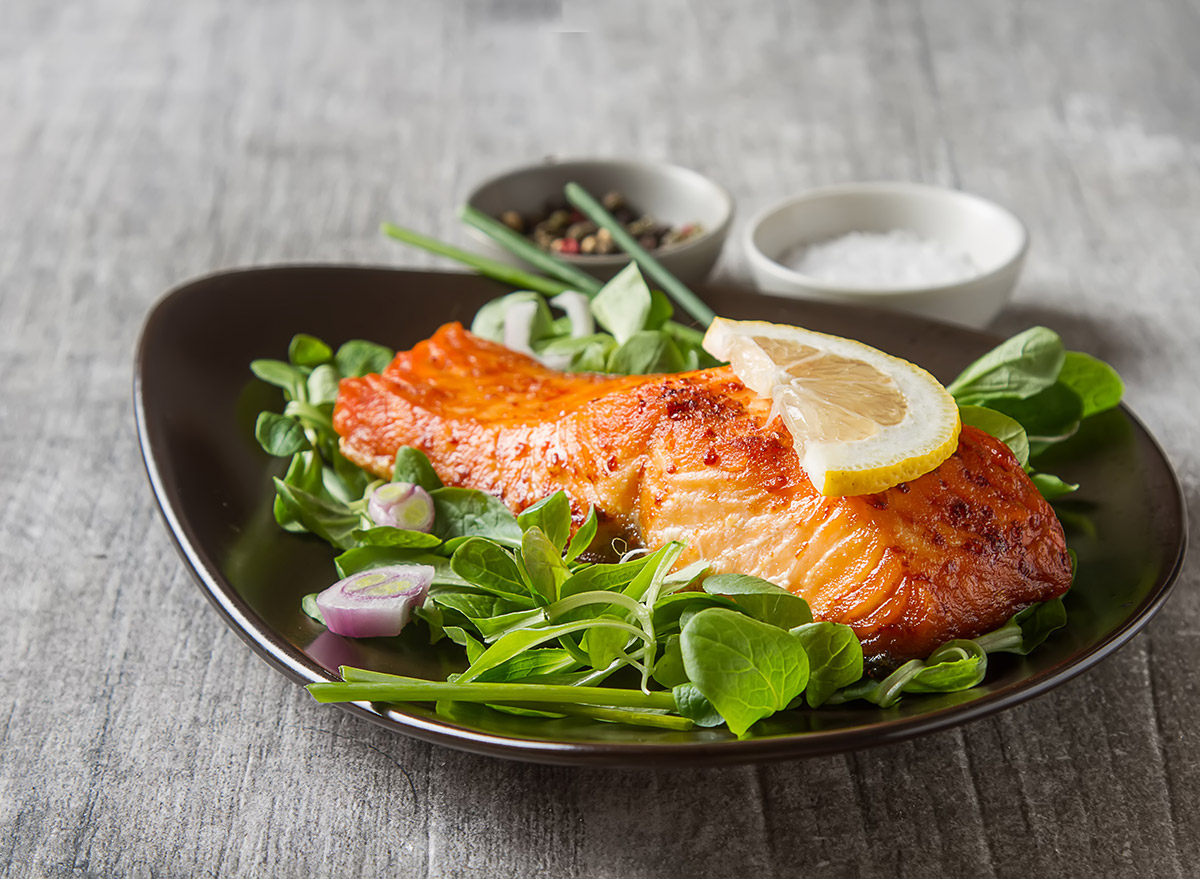 grilled salmon on a bed of spinach topped with a lemon