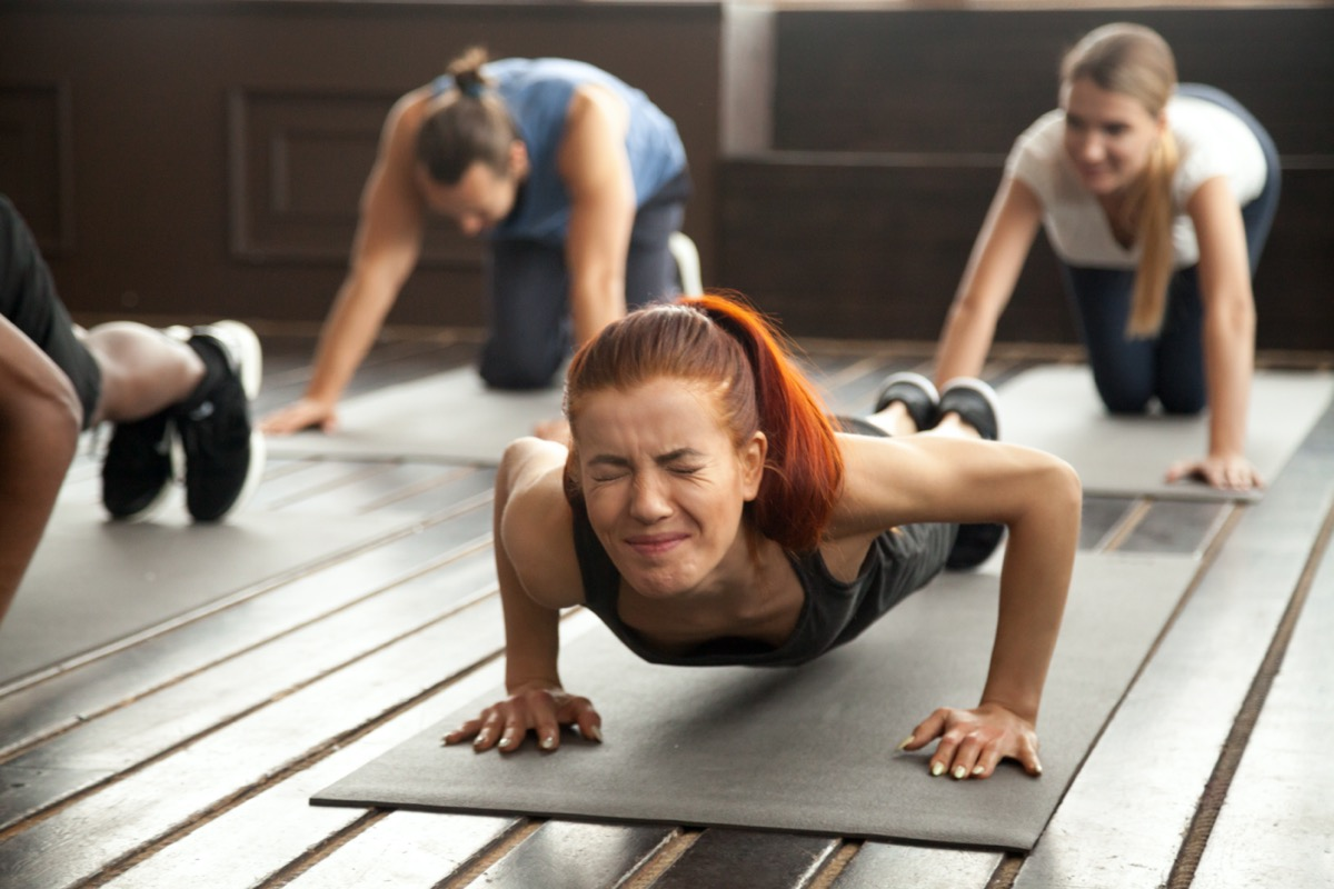 woman with painful face expression doing hard difficult plank fitness exercise or push press ups feeling pain in muscles at diverse group training class in gym