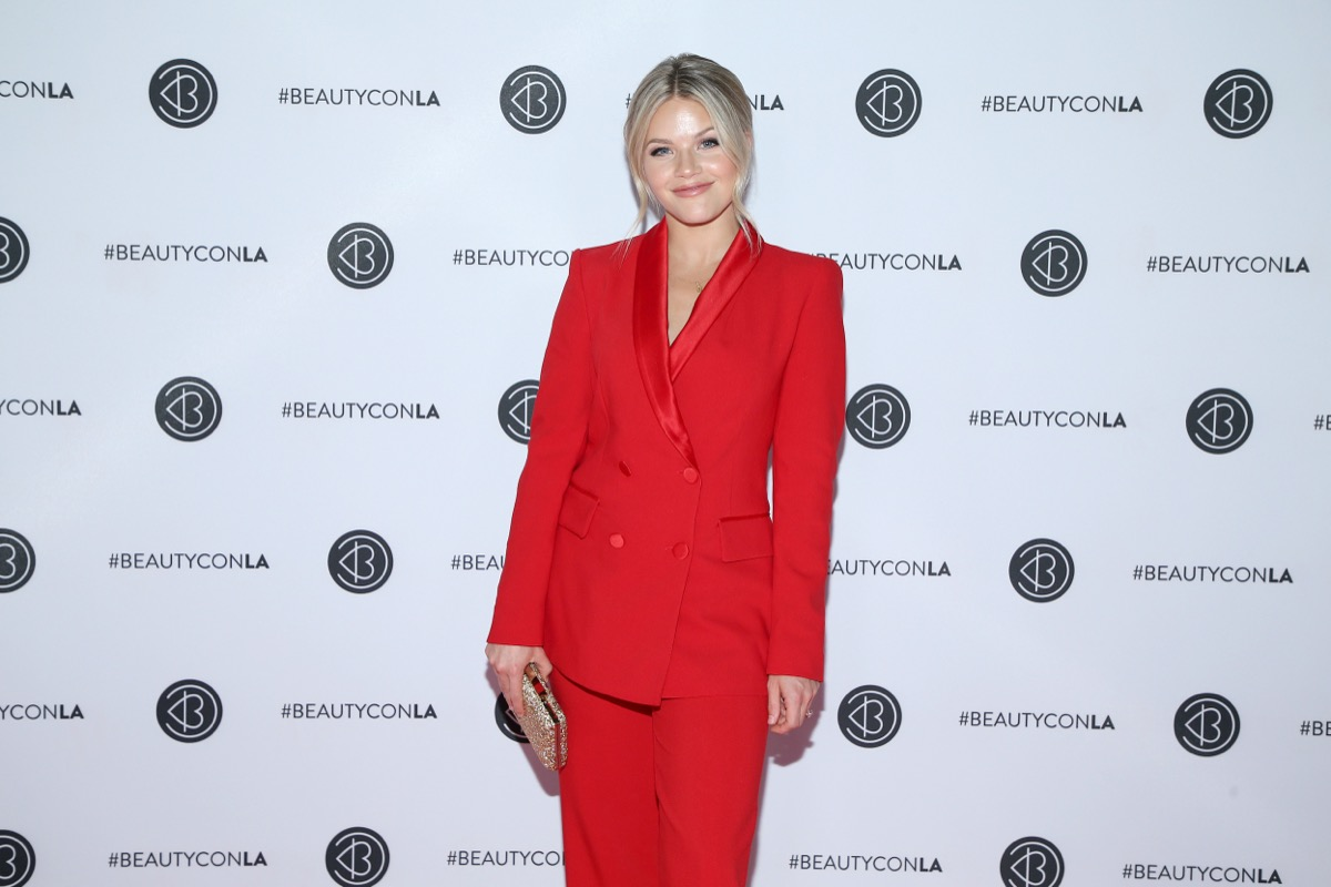 witney carson in red suit in front of white step-and-repeat