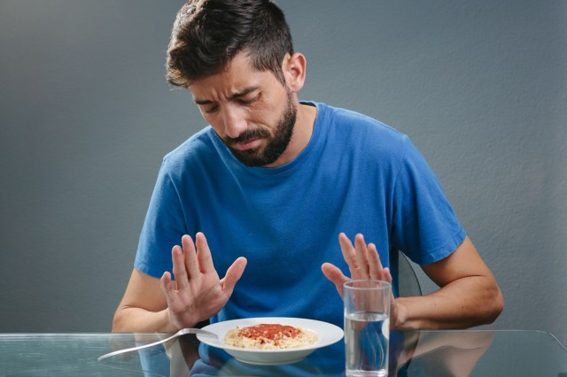 Portrait of man with no appetite in front of the meal