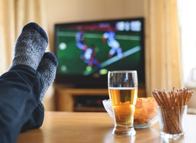 Man watching a sports game on tv while sitting on a couch eating junk snacks and drinking a beer