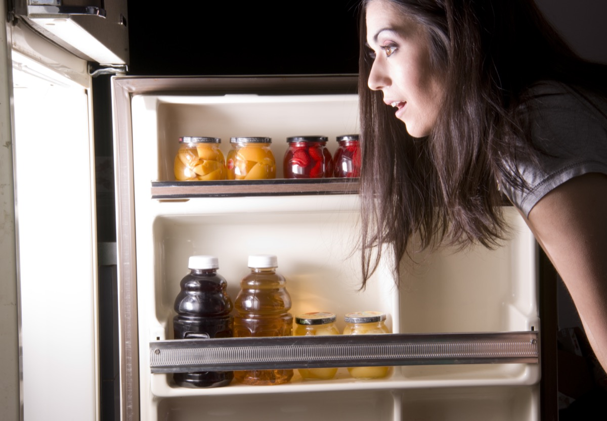 A woman raids the refrigerator late at night looking for a food snack.