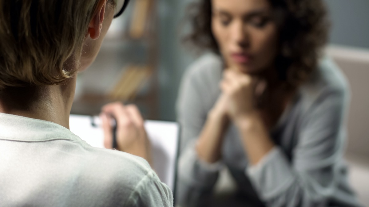 depressed woman talking to lady psychologist during session, mental health