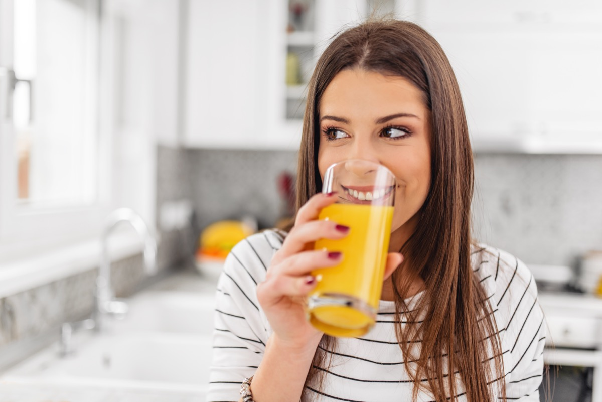 Woman drinking juice while looking through a window.