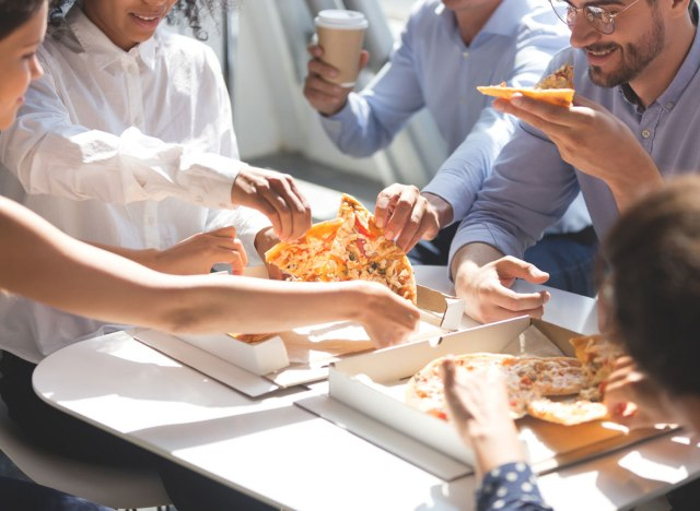 Coworkers quickly grabbing slices of pizza at work