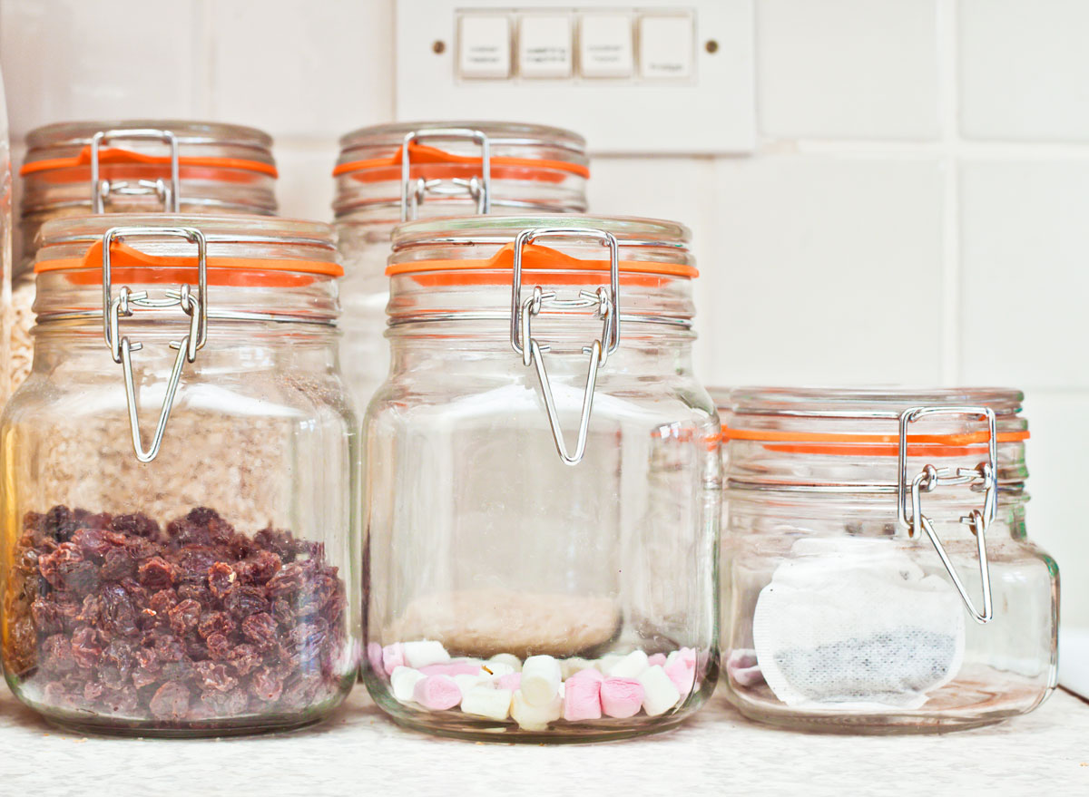 Candy and snacks visible in glass transparent containers on kitchen counter