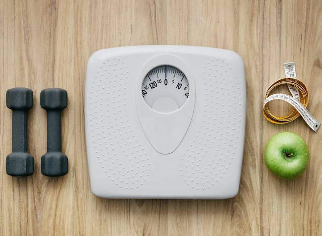 dumbbells sitting next to a scale with measuring tape and a green apple