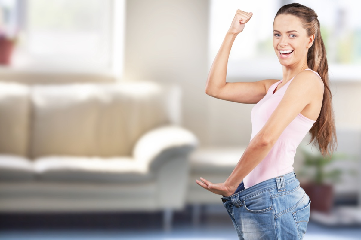 Young happy woman celebrating weight loss and showing her jeans.