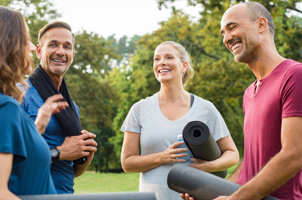 group of mature people holding yoga mat and towel in conversation after exercising at park