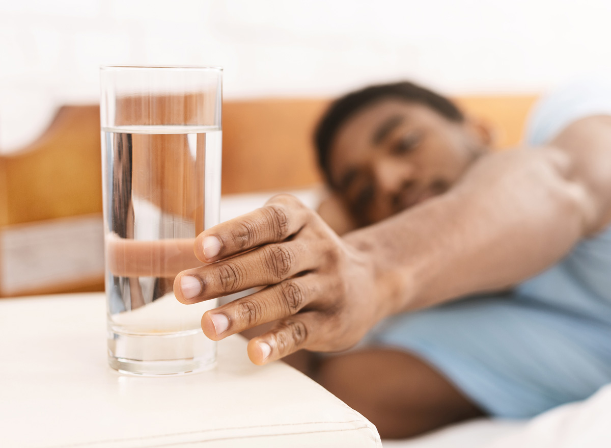 Black man reaching for a glass of water from his bed in the morning