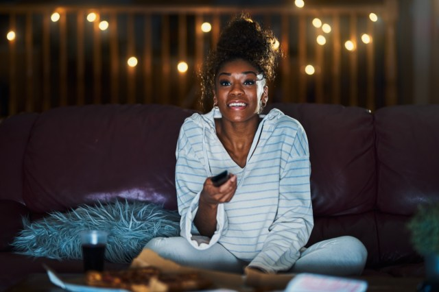 woman in pajamas staying up late at night eating pizza and watching tv