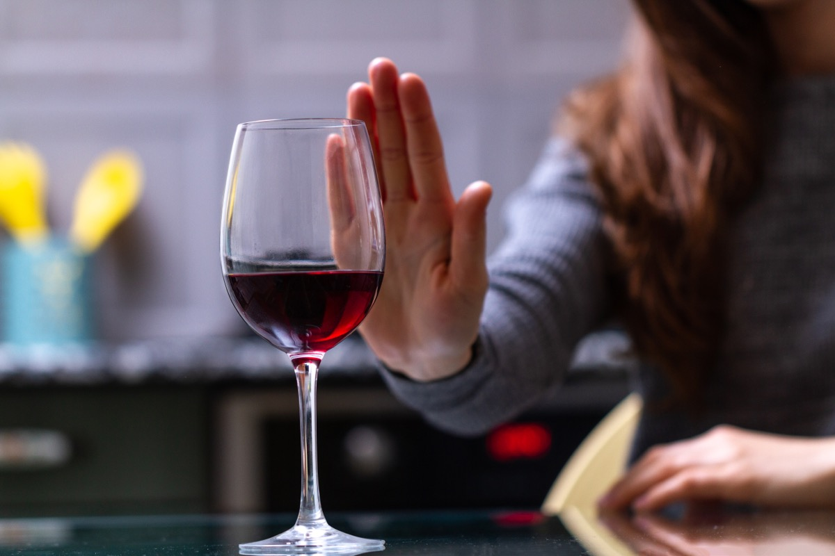 woman turning down glass of red wine