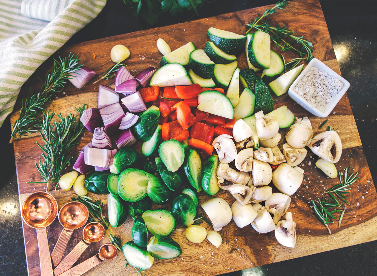 Meal prep chopped veggies brussels sprouts onions mushrooms peppers zucchini on wooden cutting board