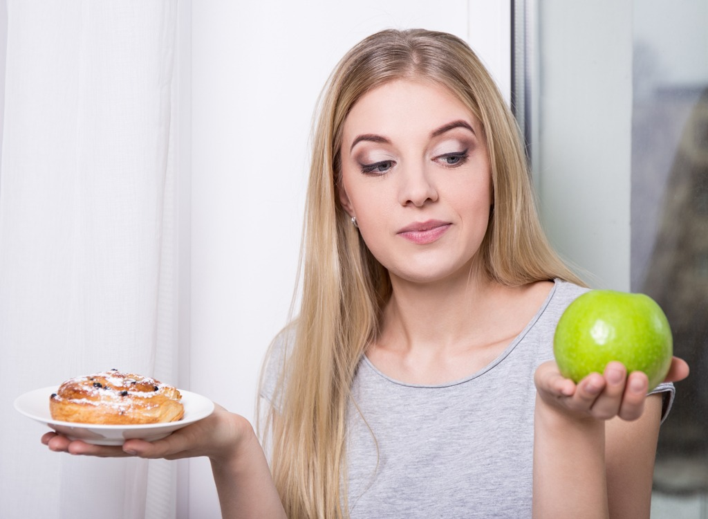Woman choosing apple over sugar-filled pastry